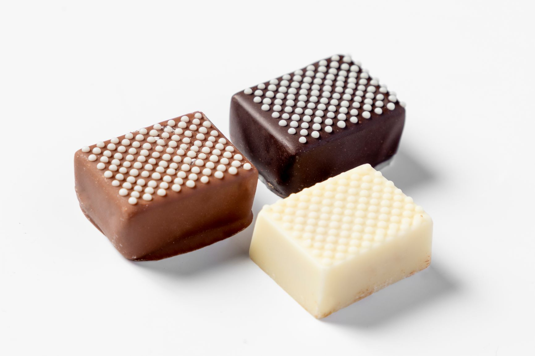 Three chocolate pralines decorated with a FoodJet chocolate depositor