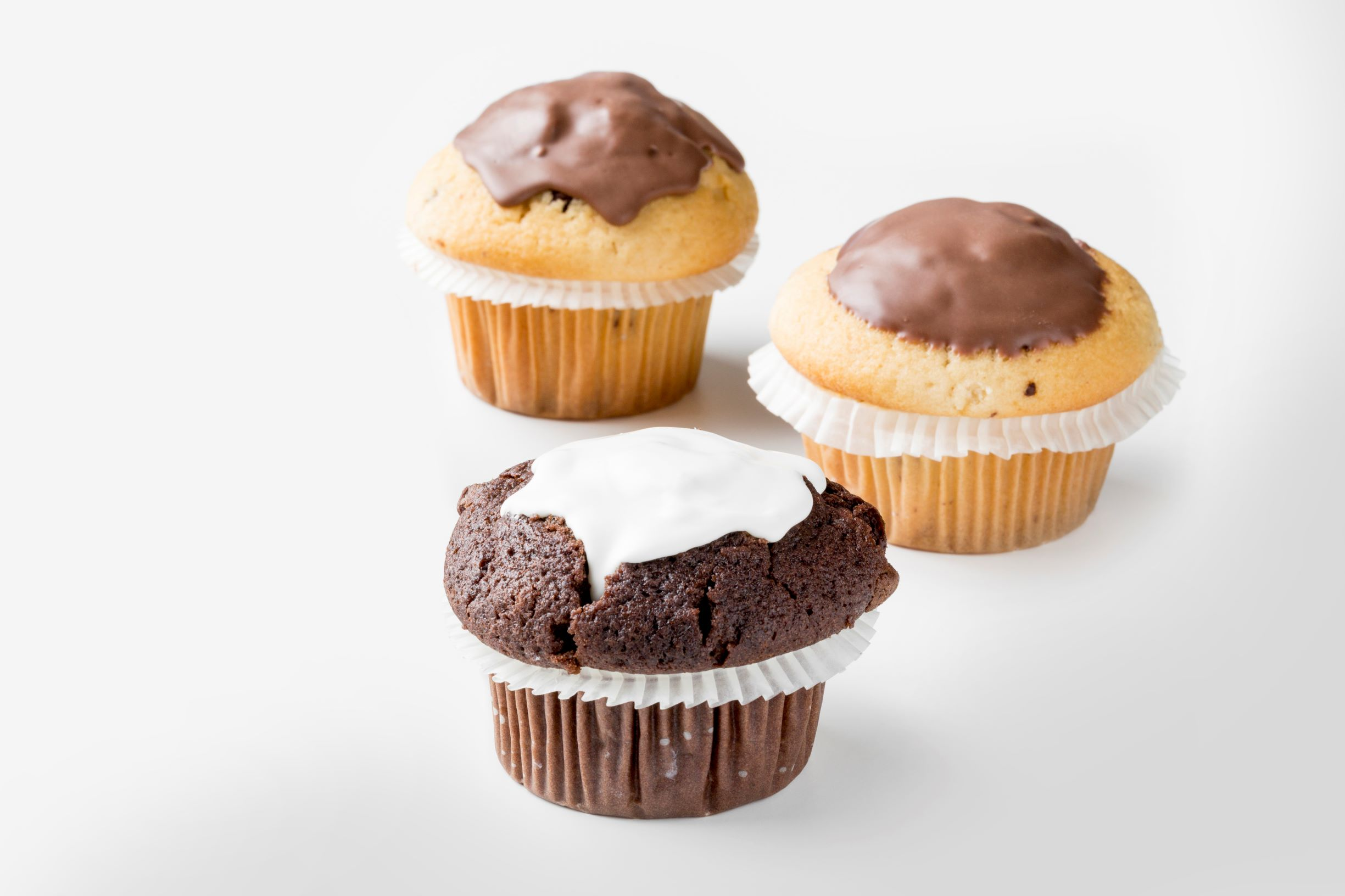 Three muffins covered with white and milk chocolate by FoodJet chocolate depositor