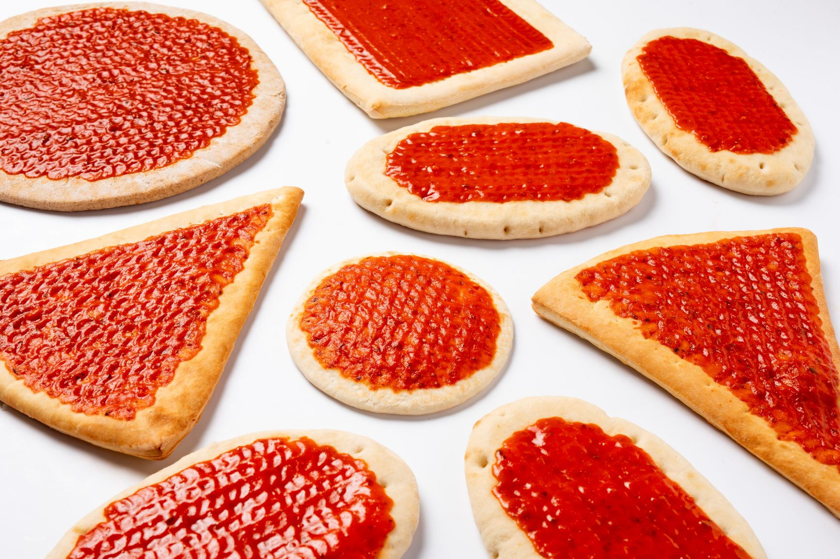 Various shapes of pizza slices with pizza sauce printed on them by a FoodJet depositor