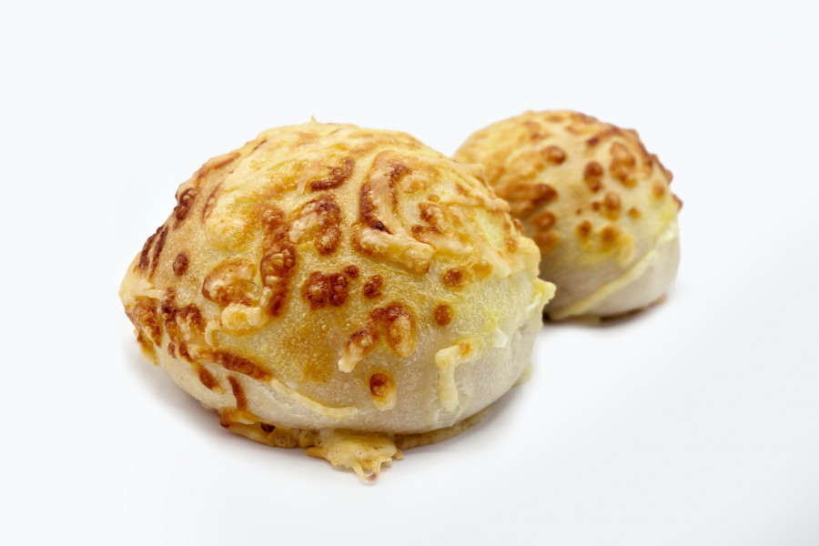 Two buns covered with liquid cheese by a FoodJet precision depositor