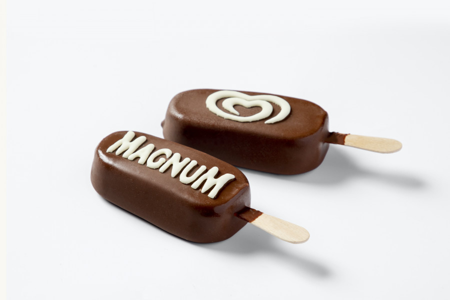 Two milk chocolate enrobed ice creams decorated with white chocolate by  a FoodJet food depositor