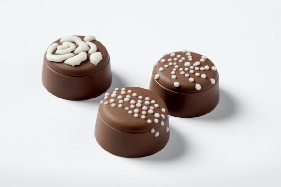 Three milk chocolate pralines decorated with white chocolate by a FoodJet precision depositing system