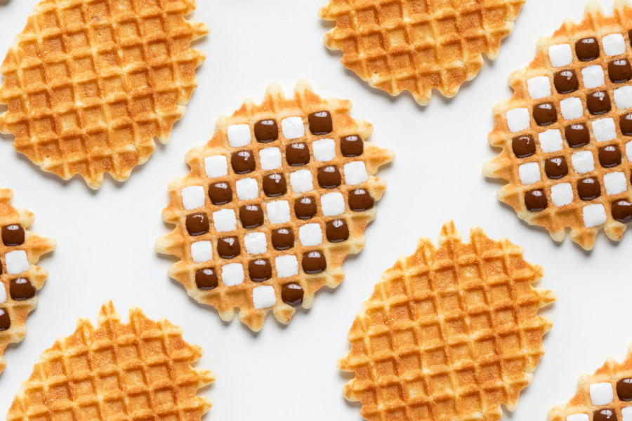 Various hard waffles cavities filled in a check board pattern with white and milk chocolate by a FoodJet precision depositing system