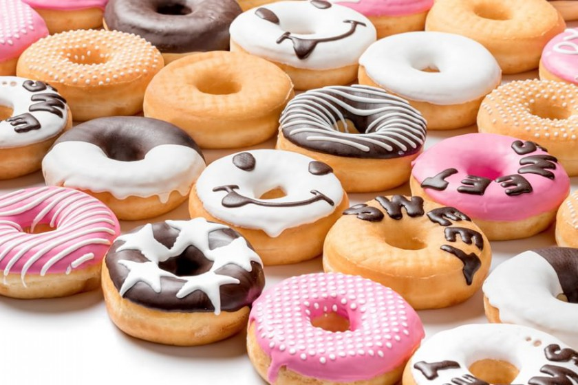 Many donuts enrobed with chocolate and decorated with white chocolate by a FoodJet precision depositing system